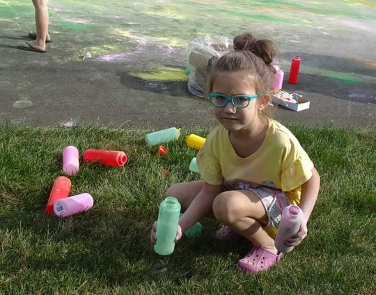 Noelle Love, 5, prepares to toss colored cornstarch on runners during the Bucyrus Bratwurst Festival 5K Color Run/Walk on Saturday morning.