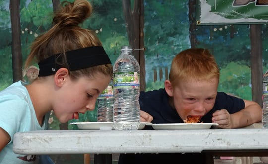 Macie Hubble and Braxton Hall compete in the pizza-eating contest Friday at the Bucyrus Bratwurst Festival.