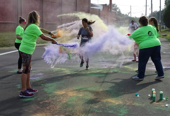 Volunteers toss colored cornstarch onto runners at Plants Way and River Street during the Bucyrus Bratwurst Festival 5K Color Run/Walk on Saturday morning.