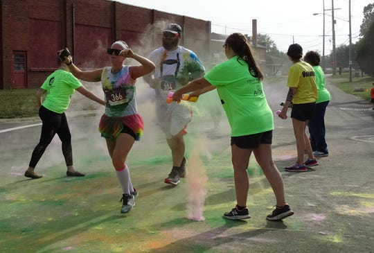 Volunteers toss colored cornstarch onto runners Ashlee Phillips and Robert Ford Jr. at Plants Way and River Street during the Bucyrus Bratwurst Festival 5K Color Run/Walk on Saturday morning.