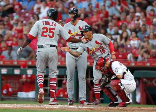 Aug 16, 2019; Cincinnati, OH, USA; St. Louis Cardinals center fielder Dexter Fowler (25) reacts with starting pitcher Adam Wainwright (50) and second baseman Kolten Wong (16) after hitting  a three run home run against the Cincinnati Reds during the second inning at Great American Ball Park.