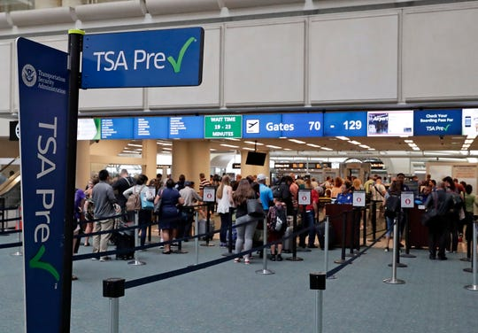 FILE- In this Thursday, June 21, 2018 photo, air passengers heading to their departure gates enter TSA pre-check before going through security screening at Orlando International Airport, in Orlando, Fla. Investigators were unable to corroborate specific allegations that a Transportation Security Administration supervisor instructed air marshals to racially discriminate against passengers at Florida's busiest airport. But investigators for the Department of Homeland Security's Office of Inspector General uncovered other concerns about racial profiling of passengers by other TSA supervisors at Orlando International Airport, according to a report sent to lawmakers last week. (AP Photo/John Raoux)