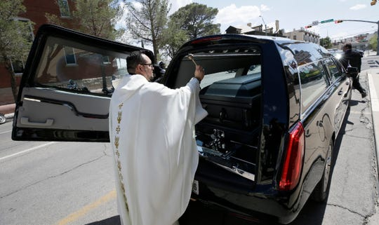 The Rev. Fabian Marquez blesses the casket of Andre Anchondo following his funeral Mass Friday, Aug, 16, 2019 in El Paso, Texas. Anchondo was one of the 22 killed in the mass shooting at Walmart on August 3.