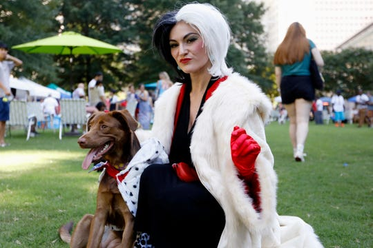 Atlanta-area resident Megan Nelson poses for a photo with her dog Darla during Doggy Con in Woodruff Park, Saturday, Aug. 17, 2019, in Atlanta. Nelson wore a Cruella de Vil costume and dressed her mixed chocolate Labrador Retriever in a Dalmatian outfit. The pair won the costume contest award for best dog and owner combination.