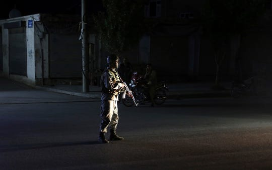 An Afghan police man stand guard outside the wedding hall after an explosion in Kabul, Afghanistan, Sunday, Aug.18, 2019. An explosion ripped through the wedding hall on a busy Saturday night in Afghanistan's capital and dozens of people were killed or wounded, a government official said. Hundreds of people were believed to be inside.