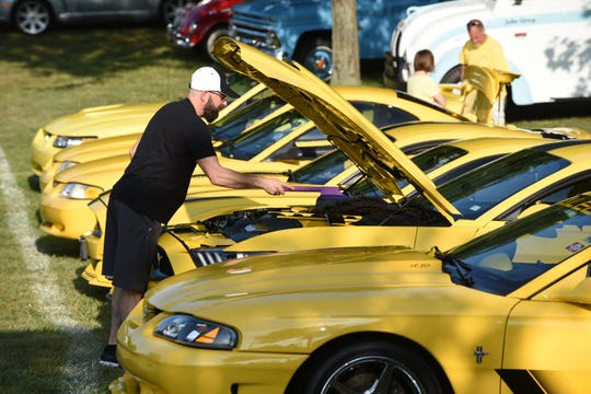Darren Bender wipes down his 2016 Ford Mustang GT at Memorial Park in Royal Oak for the Woodward Dream Cruise as he takes his spot in the Yellow Mustang Registry gathering on Saturday.