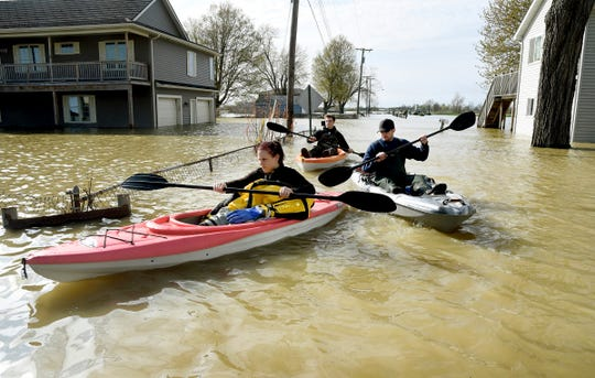 Estral Beach firefighters Courtney Millar, Eric Bruley, and Chase Baldwin kayak in floodwaters in the south end of Estral Beach May 8, in Berlin Township, Michigan, checking for evacuations.
