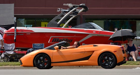 An orange Lamborghini passes a parked boat along southbound Woodward in Birmingham during an August Woodward Dream Cruise.