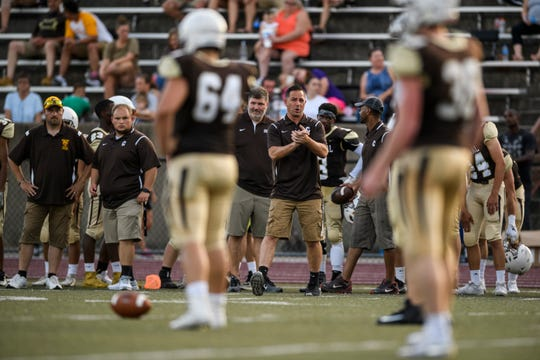 Central's new Head Coach Sean Coultis, center, watches his team from the sidelines during a pre-season scrimmage against the Gibson Southern Titans at Central Stadium in Evansville, Ind., Friday, Aug. 16, 2019.
