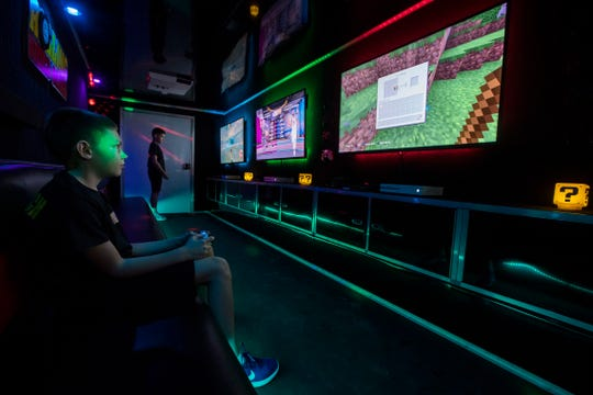 From left, brothers Liam and Connor O'Hare play inside the Rolling Video Games trailer which was stationed along First Street  in Downtown Fort Myers during the Music Walk event Friday August 16, 2019.