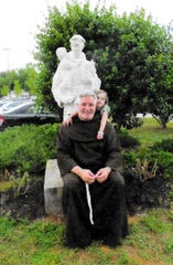 Father Patrick Tuttle poses beneath a statue of St. Anthony of Padua.