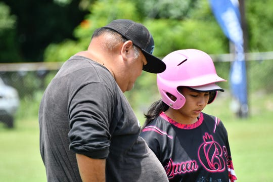 Queen Bs manager Mike Perez discusses strategy with a baserunner during his team's win against the Warriors Aug. 17 at Piti Baseball Field