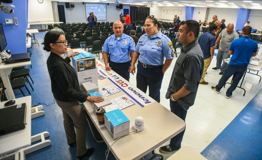 Outbound Service Coordinator Irene De Vera, left, and Service Manager Roland Villaverde, are on hand to answer questions on home surveillance products on display by Megabyte Computer Sales & Service Center, during a Neighborhood Watch Program event at the Guam Community College in Mangilao on Saturday, Aug. 17, 2019. The event was hosted by the Guam Police Department, the Guam Community College and the Mayors' Council of Guam.