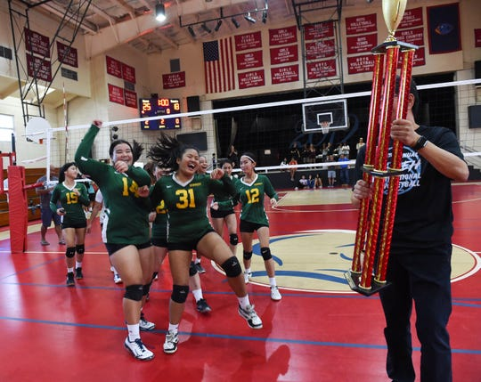 The John F. Kennedy Islanders celebrate on their way to collect a trophy from Dr. Thomas Shieh following their championship win over the George Washington Geckos for the 20th Annual Shieh Pre-Season Volleyball Tourney in the Dale Jenkins Gymnasium at St. John's School on Aug. 17, 2019.