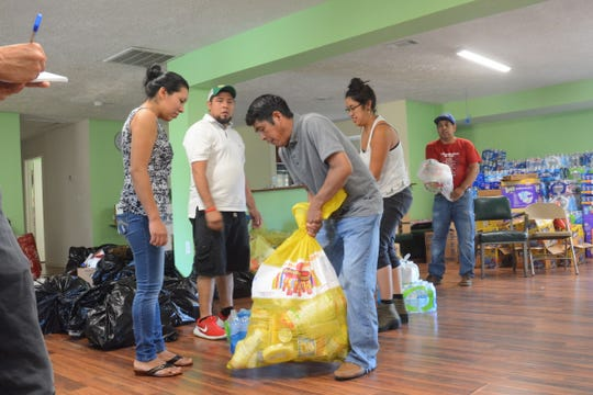 A team of volunteers and parishioners at  St. Anne Catholic Church in Carthage on Saturday, Aug. 17, 2019, dole out donated items for families in need following a federal immigration raid in Mississippi on Aug. 7, 2019. A poultry processing plant in Carthage was among those targeted.