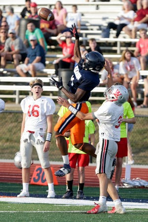 Harrison wide receiver Zion King (81) reaches up for a pass over West Lafayette wide receiver Sam Montes (32) during a preseason scrimmage, Friday, Aug. 16, 2019 at Harrison High School in West Lafayette.