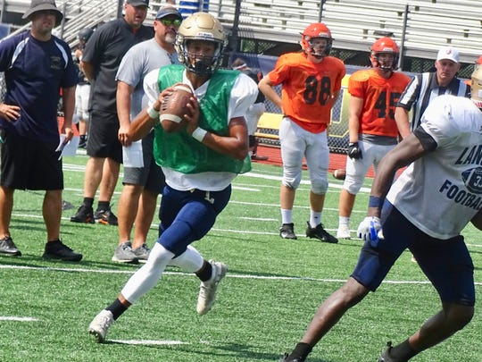 Lancaster quarterback Titan Johnson rolls out to pass during Saturday's scrimmage against North Canton Hoover.