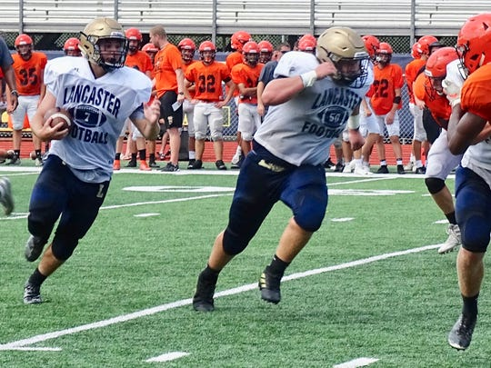 Lancaster running back Cole Smith looks for running room behind the blocking of Anthony Smith during the Gales' scrimmage against North Canton Hoover on Saturday.