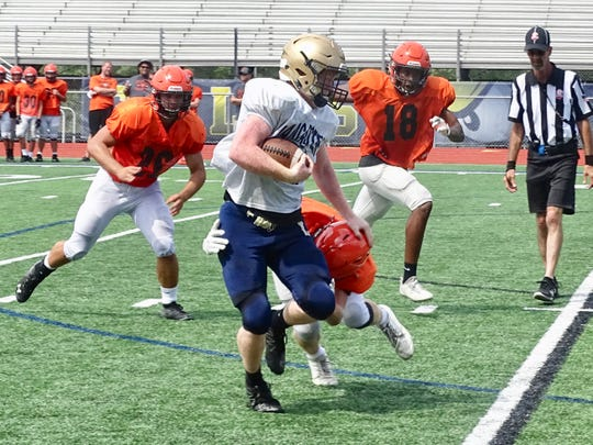 Lancaster's Sage Hill breaks a tackle during Saturday's scrimmage against North Canton Hoover.