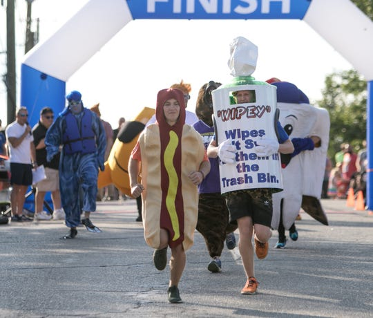The Hot Dog, representing Tony's Dogs keeps ahead of Wipey, for the Livingston County Drain Commission in the Mascot Dash, part of the Howell Melon Festival Friday, Aug. 16, 2019.