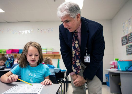 Collierville superintendent Gary Lilly goes over math problems with Sycamore Elementary School first grader Jordan Anthony.