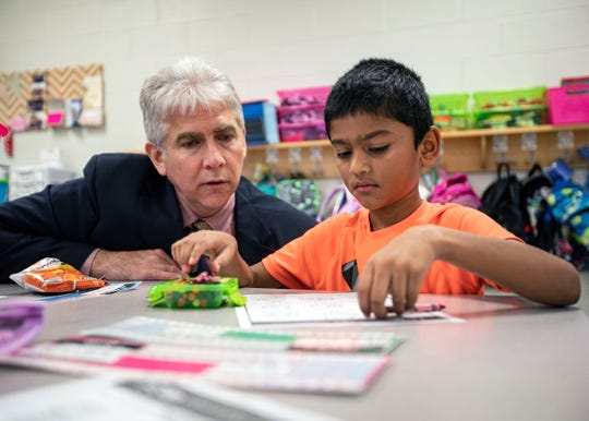 Collierville superintendent Gary Lilly goes over math problems with Sycamore Elementary School first grader Srihith Gunukota.