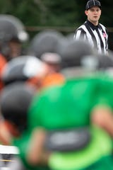 A referee looks as football players from Milwaukee Riverside and Greendale high schools play at Greendale High School's Gavinski Stadium in Greendale, Wis. during a scrimmage featuring Greendale, Brookfield East, Racine Horlick and Milwaukee Riverside on Friday, August 16, 2019.
