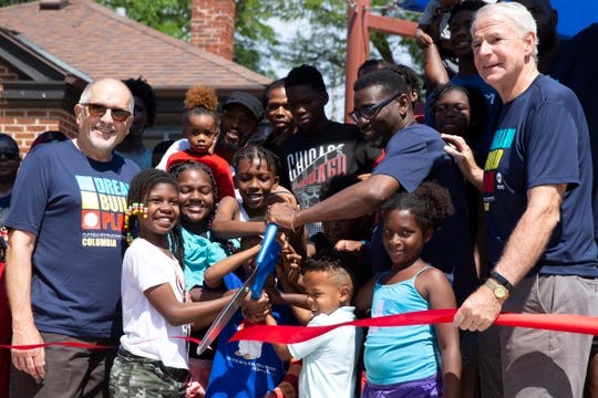 Milwaukee Public Schools Board Larry Miller, left, Superintendent Keith Posley and Mayor Tom Barrett and children cut the ribbon during a ceremony at the newly-renovated Columbia Playfield in Milwaukee Saturday.