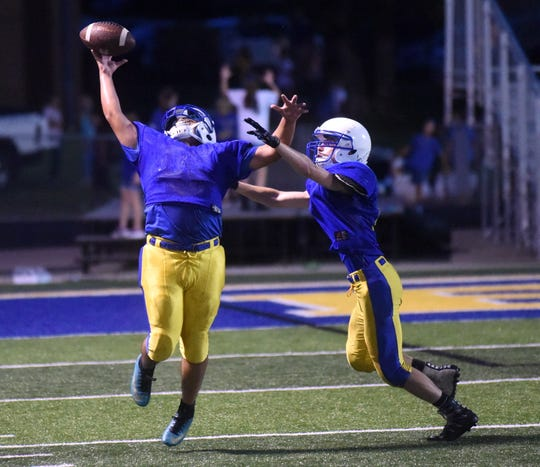 Two Mountain Home Bombers battle for the ball during a defensive back drill during practice Friday night.