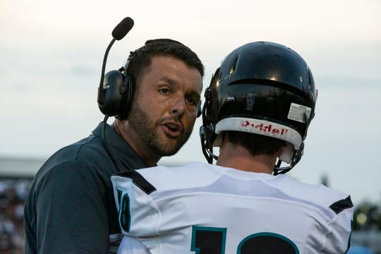 Tom Scalise, the head coach of Gulf Coast High School, talks to Bryce Allen of Gulf Coast High during the game on Friday, Aug. 16, 2019, at Staver Field of Naples High School.