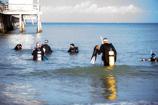 Volunteer scuba divers prepare to inspect the Naples Pier during an underwater cleanup project, Saturday, Aug. 17, 2019 in Naples.
