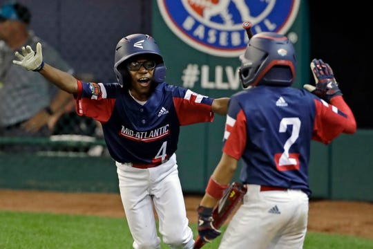 Elizabeth, New Jersey's Josiah Sharpe (4) celebrates with Yamil Soto (2) on his way to the dugout after scoring on a single by Justin Labrador during the fifth inning of a baseball game against Salem, Oregon, at the Little League World Series tournament in South Williamsport, Pa., Friday, Aug. 16, 2019.