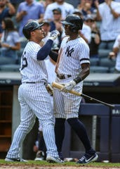 Aug 17, 2019; Bronx, NY, USA; New York Yankees shortstop Gleyber Torres (25) is greeted by right fielder Cameron Maybin (38) after hitting a solo home run in the fourth inning against the Cleveland Indians at Yankee Stadium.