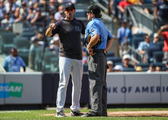 Aug 17, 2019; Bronx, NY, USA; New York Yankees manager Aaron Boone (17) argues with home plate umpire Ben May (97) in the sixth inning against the Cleveland Indians at Yankee Stadium.
