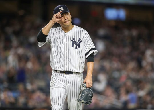 Aug 16, 2019; Bronx, NY, USA; New York Yankees pitcher Masahiro Tanaka (19) tips his cap to the crowd after being taken out in the seventh inning against the Cleveland Indians at Yankee Stadium.