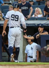 Aug 16, 2019; Bronx, NY, USA; New York Yankees manager Aaron Boone (17) congratulates right fielder Aaron Judge (99) after he scored a run in the first inning against the Cleveland Indians at Yankee Stadium. Mandatory Credit: Wendell Cruz-USA TODAY Sports