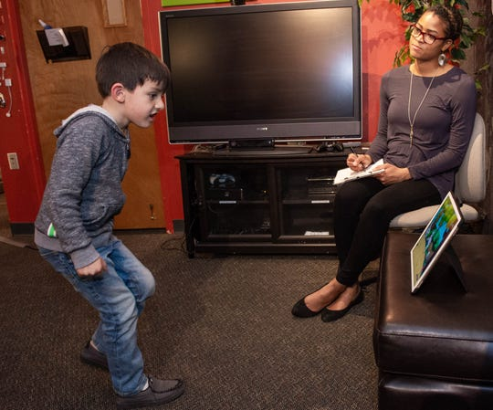 Amanda L. Armstrong, right, Games Lab Coordinator at the Innovative Media Research and Extension demonstrates how the team in the lab would observe children as they test out new games and software, with the help of Oscar Aguirre, 6,  who was testing out one of the labs prototype exercise related games on Feb. 6, 2019.