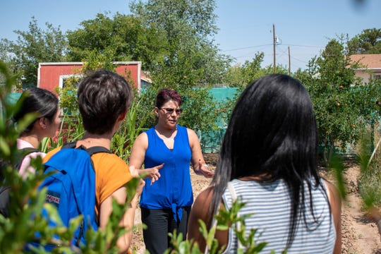 Olivia Figueroa, the executive director of Adults and Youth United in Development Association, Inc. (AYUDA) in San Elizario, Texas, speaks to students inside the organization's community garden. The students from New Mexico State University and the University of Washington spent the morning with the organization as part of the Health Disparities Field Experience. The students learned about the variety of services AYUDA offers to local low-income families, including educational courses, food distribution, physical fitness classes and immigration assistance.