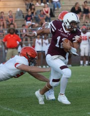 Pensacola High School quarterback Nate Simmons (12) takes to the gridiron against cross-town rivals Escambia High School for a preseason game on Friday, Aug. 16, 2019.