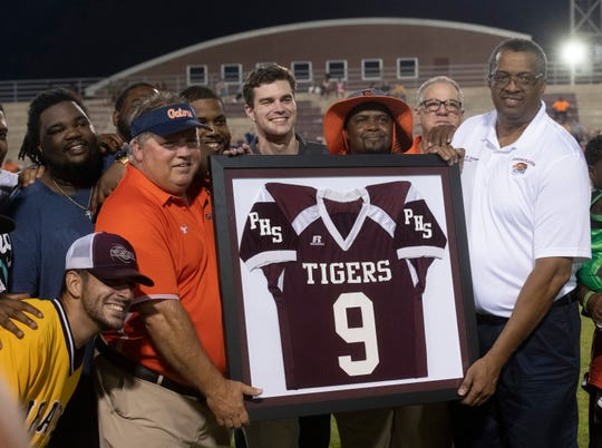 Pensacola High School Principal David Williams presents former coach Mike Bennett with a commemorative jersey to celebrate the Tigers 2009 championship season. Bennett, the former football coach at PHS, led to the team to a state championship victory 10-years ago.