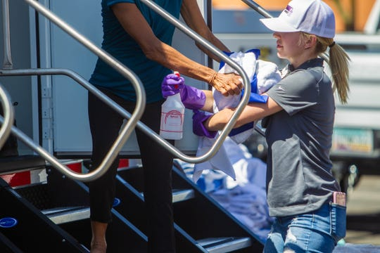 Volunteer Karli Horner, right, gives a woman supplies as she goes in to use a portable shower at the Human Services Campus in Phoenix on Aug. 17, 2019. Thunder Showers brought in a trailer of their portable showers for people experiencing homelessness to clean off and get a shave.