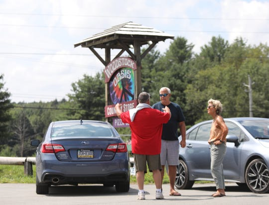 Kevin Colston, left, talks with Louis Little and Sarah Hazelgrove from Richmond Virginia, outside the Woodstock Oasis Country Store in Bethel on Saturday, August 17, 2019.