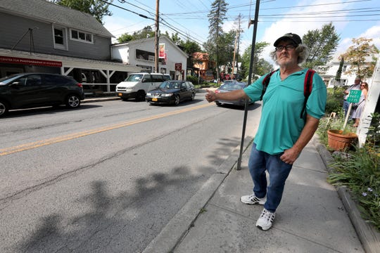 Gerard Paturel, 59,of Woodstock, N.Y. hitchhikes his way out of town Aug. 17, 2019. Patrol has lived in Woodstock for most of his life. Paturel's father rented Bob Dylan a room over Cafe Espresso,  which he owned in the 1960's. Dylan wrote his first three albums while living there. People flocked to the historic town on to mark the 50th anniversary of the Woodstock festival, which took place in Bethel, N.Y., 70 miles from Woodstock.