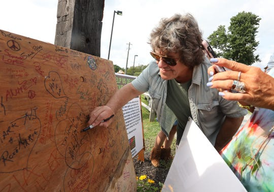 Original Woodstock promoter Michael Lang signs a gun control petition on a piece of the original Woodstock stage at the Catskill Distillery and the Dancing Cat Saloon in Bethel on Saturday.