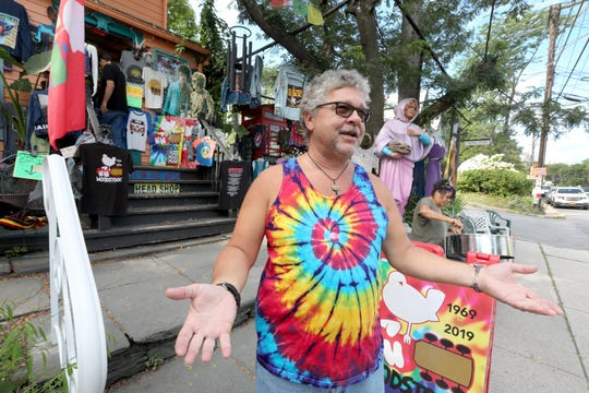 Gregory Adami, 55, of North Amityville, Long Island, stands outside Legends, a souvenir and head shop in Woodstock, N.Y. Aug. 17, 2019. Adami has been coming to Woodstock on the anniversary of the historic Woodstock festival for the last 27 years. People flocked to the historic town to mark the 50th anniversary of the festival, which took place in Bethel, N.Y., 70 miles from Woodstock.