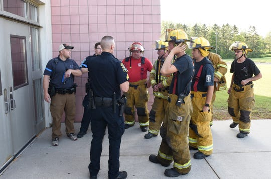 Sergeant Brent Bukowski of the Sauk Rapids Police Department speaks with firefighters who have arrived on scene for the active threat training Wednesday, Aug. 14, 2019, at Sauk Rapids-Rice Middle School.