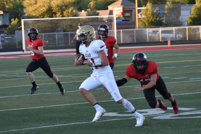 Juab quarterback Zac Cowan runs away from a Hurricane defender.