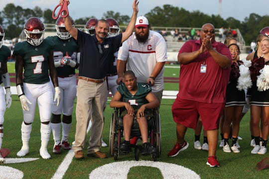 Leon County Schools Superintendent Rocky Hanna cuts a ribbon with the help with Chiles High School student Shareef Gaymon, center, marking the first game on the new turf at Chiles High School Friday, August 16, 2019.