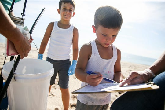"Levi Ricciuti (center), 4, tallies the trash that he and his brother Eli (left), 6, of Vero Beach, collected during the third coastal cleanup of the year hosted by Coastal Connections at South Beach Park on Saturday, August 17, 2019, in Vero Beach. One of Coastal Connections initiatives this year is plastic reduction and part of their effort is going towards coastal cleanups. ""We just want to do our part by removing plastics and debris so we can continue to enjoy the beautiful space,"" said Kendra Cope, president of Coastal Connections. Among the many items the 30 volunteers collected were 1,015 pieces of plastic, 351 cigarette butts, 135 bottle caps and 153 plastic food wrappers."
