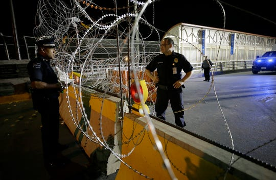 A Mexican Federal Police Officer and a Customs and Border Protection officer talk through a wall of concertina wire Friday, August, 16, 2019 between El Paso, Texas and Juarez, Chihuahua, Mexico.